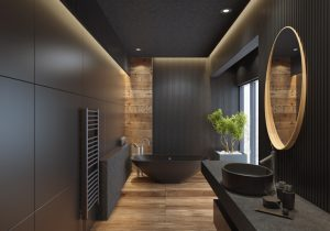 contemporary minimalist bathroom with black wooden walls and large grey matte and wood effect tiles. round mirror with wooden frame is on the wooden black wall. round grey stone washbasin and stainless steel basin tap is on top of the grey stone vanity unit with three drawers. freestanding black stone bathtub and floor mounted inox tap is on a platform with wood effect tiles. long floor tiles with wood effect. black ceiling with strip cove lighting and embedded spotlights. ***background is my istock image